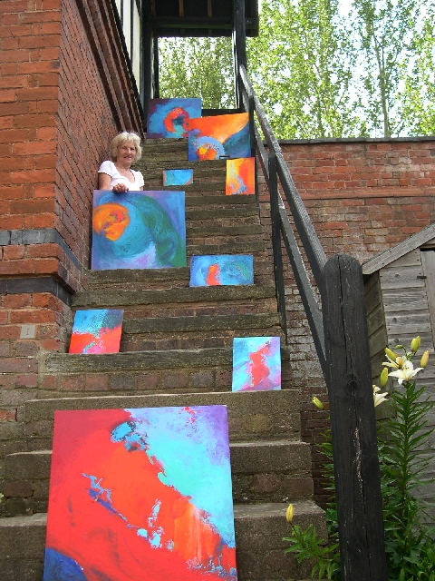 Stella Hidden, artist, with some of her colourful colorful acrylic abstract expressionist non-representational paintings on the 